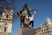 Inspired by Swedish teenager Greta Thunberg and organised by Youth Strike 4 Climate, British eco-aware school and college-age pupils protest about Climate Change stand on the statue of Winston Churchill in Parliament Square during their walkout from classes, on 15th February 2019, in Westminster, London England.