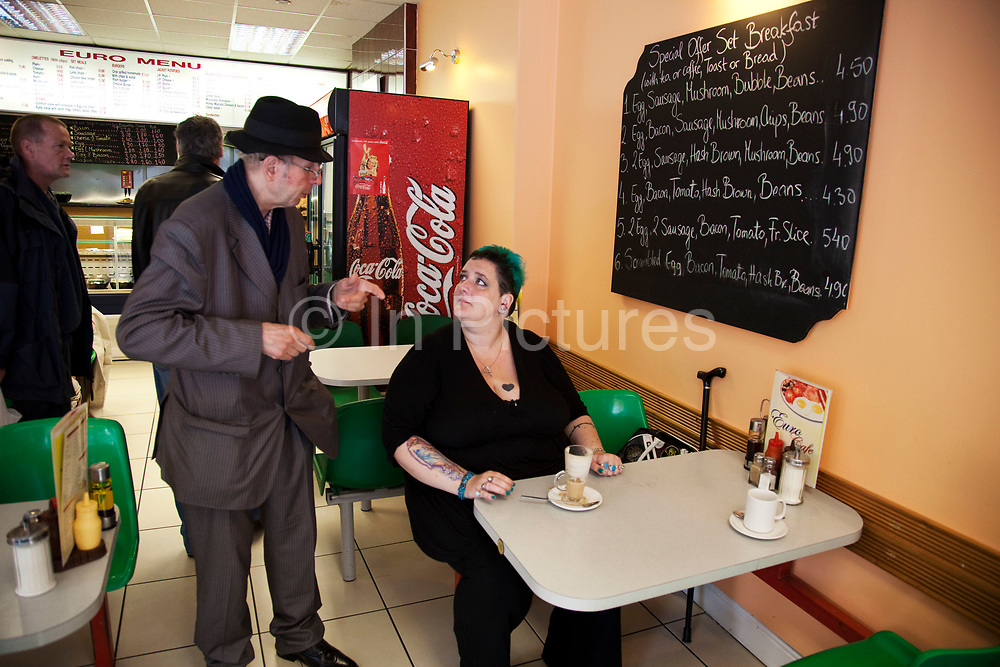 LONDON, ENGLAND, UK, JUNE 18TH 2011. Mother Louise Irwin-Ryan speak to Dave, a local Elvis impersonator in her local cafe in her neighbourhood of Barnsbury, near to Kings Cross, North London. Louise is on various benefits to help support her family income, and housing, although recent government changed to benefits may affect her family drastically, possibly meaning they may have to move out of London. Louise Ryan was born on the Wirral peninsula in 1970.  She moved to London with her family in 1980.  Having lived in both Manchester and Ireland, she now lives permanently in North London with her husband and two children. Through the years Louise has battled to recover from a serious motorcycle accident in 1992 and has recently been diagnosed with Bipolar Affective Disorder. (Photo by Mike Kemp/For The Washington Post)