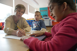 Two children sitting at desk in classroom with teacher,