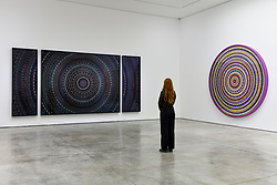 """Licensed to London News Pictures. 19/09/2019. LONDON, UK.  A staff member poses between (L to R) """"The Creator"""" 2019, and """"Radial Balance"""", 2019, both by Damien Hirst.  Preview of a new exhibition by Damien Hirst at White Cube's Mason's Yard gallery in Mayfair.  It is the artists first major solo exhibition in seven years and features large-scale concentric butterfly paintings from his new """"Mandalas"""" series.  22 large scale works are on display 20 September to 2 November 2019..  Photo credit: Stephen Chung/LNP"""