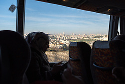 27 February 2020, Jerusalem: A woman patient travels homeward through a bus service offered by the Augusta Victoria Hospital in Jerusalem in an effort to faciliate access to medical services for patients living in the West Bank.
