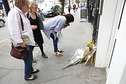 © Licensed to London News Pictures. 12/07/2019. London, UK. People look at flowers placed at the scene where a mass brawl took place in Purley, south London ending with a teenager murdered and two others injured, including the murder suspect. Photo credit: Peter Macdiarmid/LNP