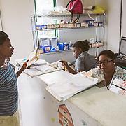 INDIVIDUAL(S) PHOTOGRAPHED: Unknown, unknown, and Viola Pierre Louis. LOCATION: Sacré-Cœur Hospital, Milot Commune, Cap-Haïtien, Haïti. CAPTION: Viola Pierre Louis, a maternity nurse at Sacré-Cœur Hospital, sits behind the desk in the maternity ward.