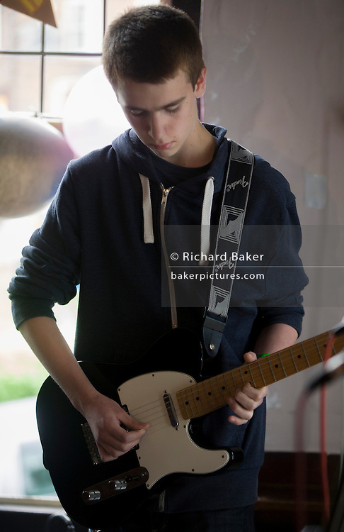 A teenage lead-guitarist playing a Fender Telecaster plays a solo during a song with his band in front of parents in an upstairs pub room in south London. 15 year-old lads play their own songs and covers by other musical artists.