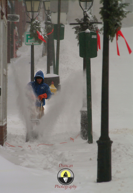 """December 16, 2007 -- BATH, Maine. Raymond """"Buck"""" Alexander blows snow from the sidewalk in front of his apartment, above the Frank Smith Cleaners in downtown Bath, on Sunday afternoon. """"A cop told me not to plow out in the road-- but then the plow guy came round and told me to go right ahead and put it out in the street. I'm goin' with the plow guy."""" He added, """"I'm helpin' out the old lady who runs the shop downstairs. She's not quite so able as I am. And this thing (the electric snow blower) is awesome!"""".Buck's fiancee, Sarah Rumery, right, and her daughters, Taylor Rumery, 3, left, and Madysin Rittall, 2, looked out the upstairs window with their neighbor Sarah Murphy, 22, as Buck cleaned up down below.  .""""Do you want some hot chocolate?"""" asked Sarah, Buck's fiancee, as Taylor and Madysin pushed snow off the window sill. Buck came upstairs and had a warm cup of cocoa after he finished up.  .Snow reached 10 inches deep in some places in Bath on Sunday.  On Sunday evening it rained, making an icy crust over the snow by dawn, as temperatures dropped into the teens.  Photo by Roger S. Duncan."""
