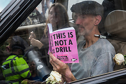 London, UK. 8 October, 2019. Climate activists from Extinction Rebellion sit locked together inside a hearse containing a coffin used to block access from Whitehall to Trafalgar Square the previous day during International Rebellion protests to demand a government declaration of a climate and ecological emergency, a commitment to halting biodiversity loss and net zero carbon emissions by 2025 and for the government to create and be led by the decisions of a Citizens' Assembly on climate and ecological justice.