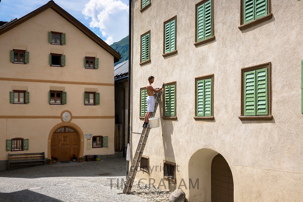 Man painting house in Engadine Valley village of Guarda with old painted stone 17th Century buildings, Switzerland