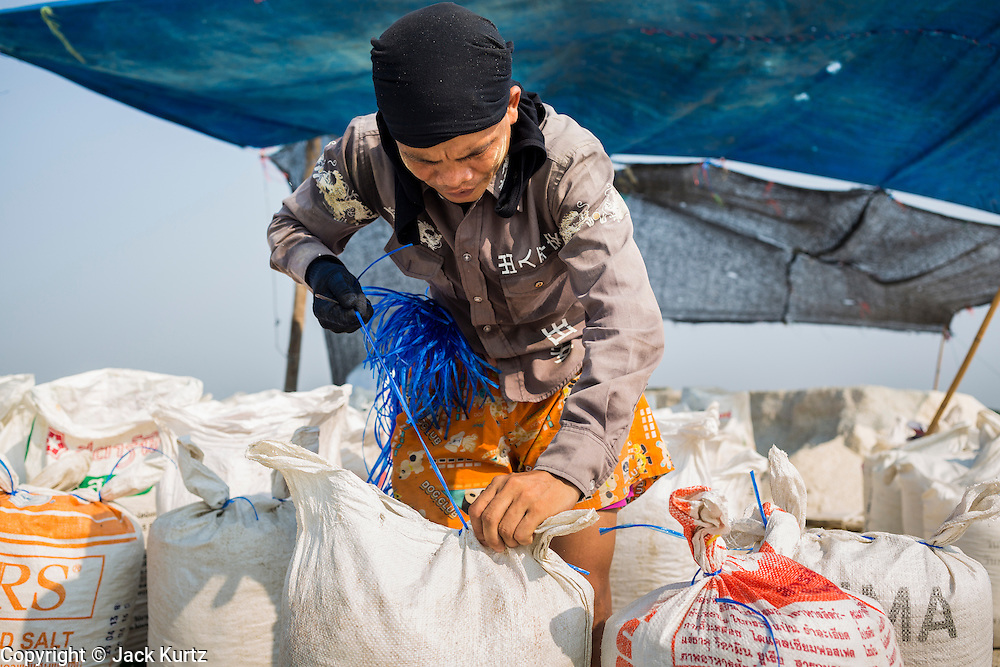 """28 MARCH 2014 - NA KHOK, SAMUT SAKHON, THAILAND: A Burmese migrant laborer sews shut a bag of salt on a Thai salt farm in Samut Sakhon province. Thai salt farmers south of Bangkok are experiencing a better than usual year this year because of the drought gripping Thailand. Some salt farmers say they could get an extra month of salt collection out of their fields because it has rained so little through the current dry season. Salt is normally collected from late February through May. Fields are flooded with sea water and salt is collected as the water evaporates. Last year, the salt season was shortened by more than a month because of unseasonable rains. The Thai government has warned farmers and consumers that 2014 may be a record dry year because an expected """"El Nino"""" weather pattern will block rain in mainland Southeast Asia. Salt has traditionally been harvested in tidal basins along the coast southwest of Bangkok but industrial development in the area has reduced the amount of land available for commercial salt production and now salt is mainly harvested in a small parts of Samut Songkhram and Samut Sakhon provinces.    PHOTO BY JACK KURTZ"""