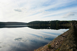 Sky reflects in the water of Langsett Reservoir on the Edge of the Peak District Shot from the dam Wall on the East side of the reservoir looking West toward Crookland Wood<br /> 07 October 2012.<br /> Image © Paul David Drabble
