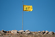 Yellow Flag of Hezbollah with a blue sky background on the Israeli Lebanese border