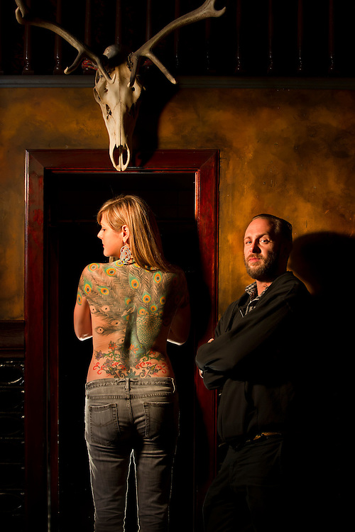 Chet Duvenci, a tattoo artist at Mercy Seat Tattoo, right, worked with Garnet Baker on creating the full-back tattoo of a colorful peacock over the course of a year at 210 East 16th Street in downtown Kansas City, Mo.