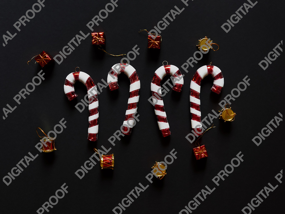 Christmas candy canes drums hearts and gifts at studio above view over a black background isolated flatlay