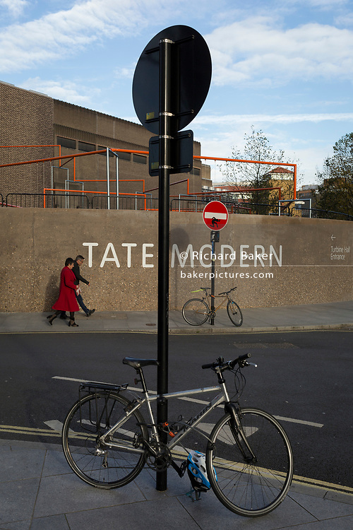 A cyclist on a Santander rental bike pedals past the Tate Modern art gallery on the Southbank, on 13th November 2017, in London, England.
