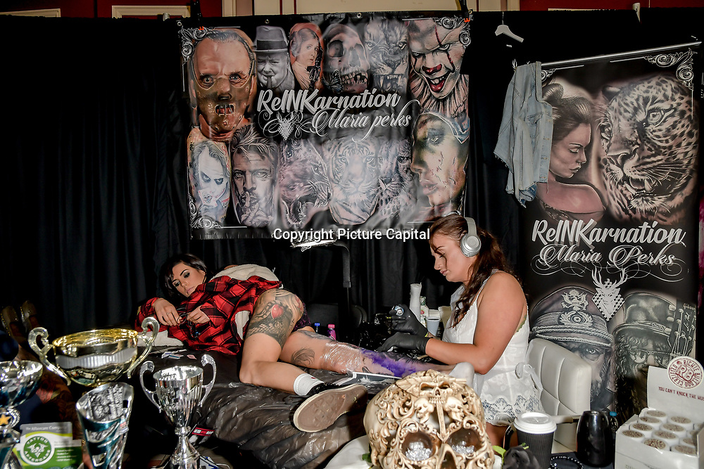 ReINKarnation artist tattoo a client at The Great British Tattoo Show, on 26 May 2019, London, UK.