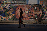 cuban man with mural in background