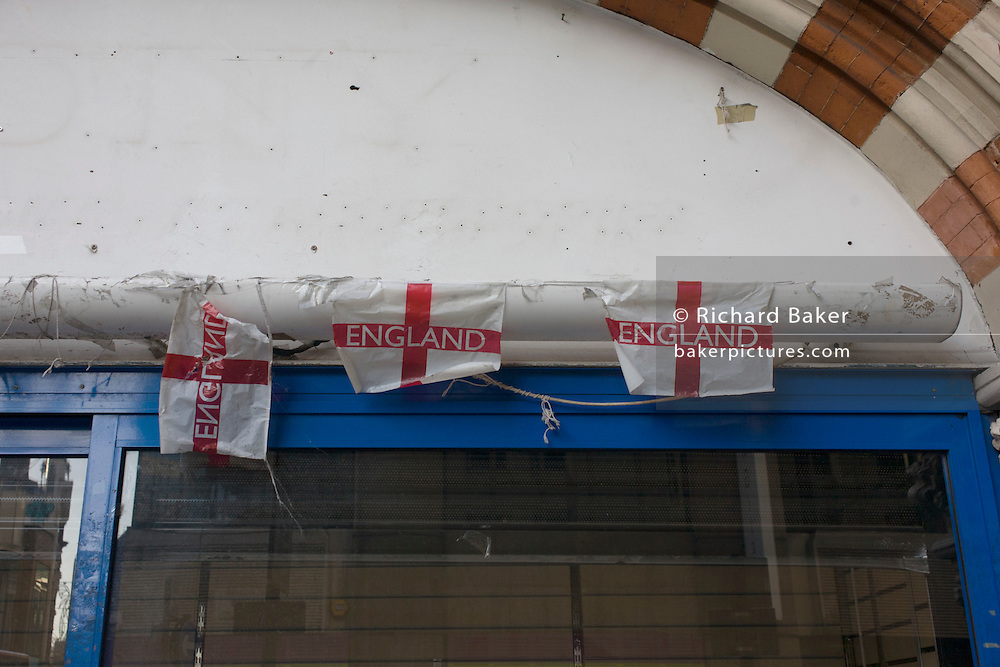 Dystopian detail of three torn English flags above the window of a closed retailer in central London.