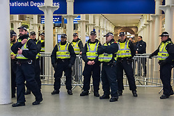 "St Pancras, London, January 16th 2016. Dozens of protesters hold an ""emergency demonstration and die-in"" as France prepares to bulldoze the Jungle Camp at Calais. PICTURED: Police watch a small group of protesters in the Eurostar terminal. ///FOR LICENCING CONTACT: paul@pauldaveycreative.co.uk TEL:+44 (0) 7966 016 296 or +44 (0) 20 8969 6875. ©2016 Paul R Davey. All rights reserved."