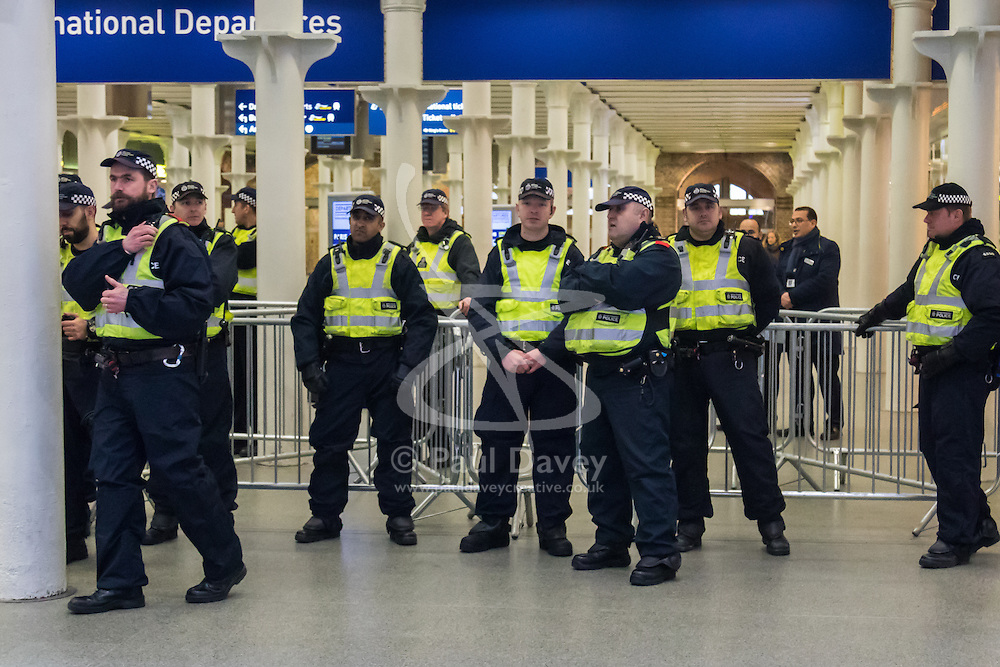 """St Pancras, London, January 16th 2016. Dozens of protesters hold an """"emergency demonstration and die-in"""" as France prepares to bulldoze the Jungle Camp at Calais. PICTURED: Police watch a small group of protesters in the Eurostar terminal. ///FOR LICENCING CONTACT: paul@pauldaveycreative.co.uk TEL:+44 (0) 7966 016 296 or +44 (0) 20 8969 6875. ©2016 Paul R Davey. All rights reserved."""