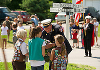 """Gilford Fire Chief Stephen Carrier assists the Girl Scouts for the """"placing of the wreath"""" on the World War I & II memorial at the start of the Memorial Day parade Monday morning.  (Karen Bobotas/for the Laconia Daily Sun)"""