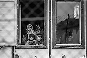 """Refugees from Bosnia in the Varazdin refugee camp in Croatia in the winter of 1992. The woman on the left is grandmother """"Nana"""" with her nephew """"Elvis"""" (second on the left, first line) and his sister Elvira beside him looking out of the  window of a barrack where they lived as refugees."""