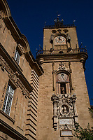 """Tower and Campanile at Aix-en-Provence - this clocktower was once the gate of the military outpost of Sextius and then the Bourg Saint Sauveur. It was constructed in 1510 and decorated with flamboyant pinnacles and ogres, and was the symbol for Aix-en-Province starting in the 14th century.  Its """"ban"""" bell emclosed in a 16th-century wrought iron cage, which was used to call the people to arms or to meet within a one-league perimeter of the city.  Today it only strikes the hours.  The clock is flanked by statues and an astronomical clock above the wooden figures of the four seasons.  An inscription commemorates the liberation of Aix in August 1944"""