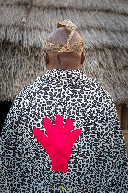 Detail of man wearing cloak with red hand that symbolizes his occupation as sangoma, or traditional healer, Eswatini