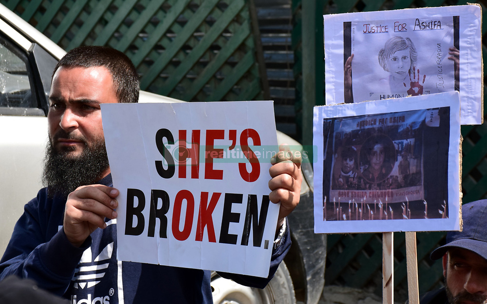 April 13, 2018 - Srinagar, Jammu & Kashmir, India - Kashmiri man seen holding a placard during the protest against the Rape and murder of Asifa and recent civilian killings  in Kulgam. Aimed curfew like restrictions in several parts of old Srinagar several protest rallies were across Kashmir valley. The Joint Resistance Leadership, an amalgam body of pro-freedom leaders, had asked people to stage peaceful protests after mandatory Friday prayers against civilian killings in Kulgam district of south Kashmir and against the rape and murder of a minor girl belonging to nomadic community in Kathua. People soon after completing Friday prayers assembled outside mosques carrying banners in their hands some of which read: ''Justice for Asifa, We want freedom and stop civilian killings,'' shouting slogans. (Credit Image: © Abbas Idrees/SOPA Images via ZUMA Wire)