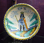 Dish, Charles II, probably London (Lambeth?) c1670-1675, inscribed CR.  The back of the dish is covered in a yellow lead-glaze which has run from the body.  Charles II is depicted in an outdoor setting.