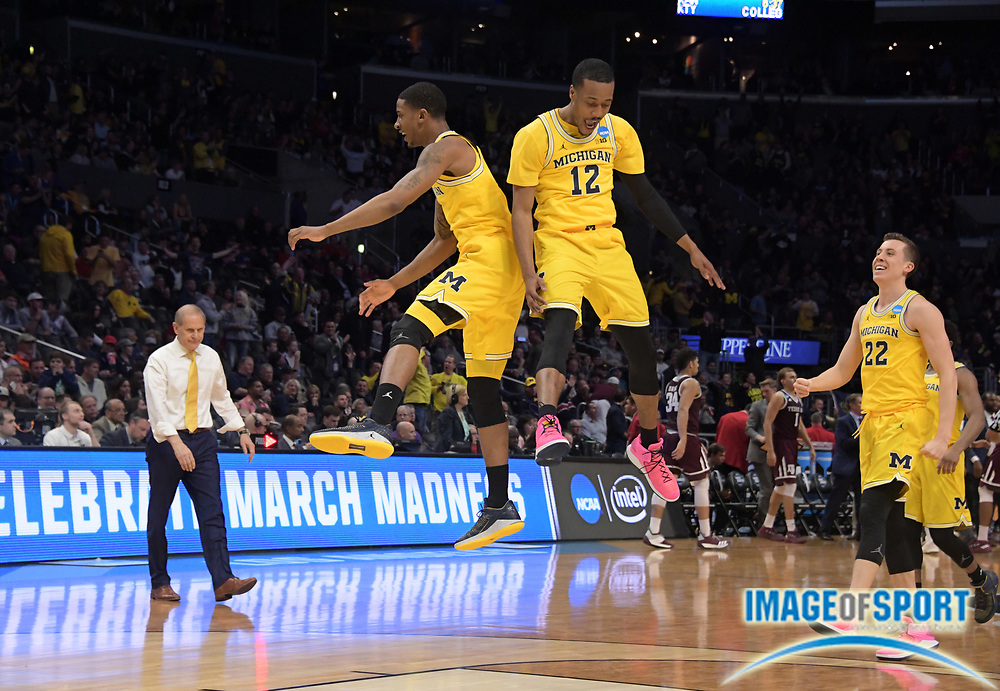 Michigan Wolverines guard Charles Matthews (1), guard Muhammad-Ali Abdur-Rahkman (12) and guard Duncan Robinson (22) celebrate as coach Jeff Beilein watches in the first half against the Texas A&M Aggies during a West Regional semifinal of the NCAA men's college basketball tournament, Thursday, March 22, 2018, in Los Angeles. Michigan defeated Texas A&M 99-72.