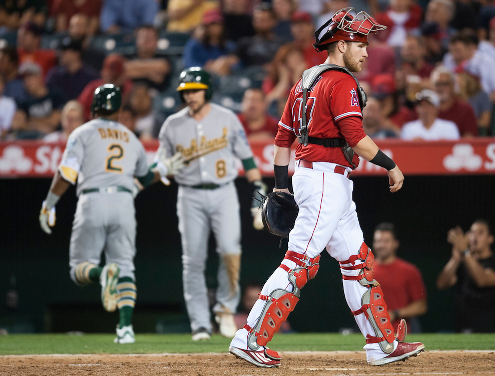Angels' catcher Jett Bandy walks back to the plate as the Athletics' Khris Davis celebrates his solo home run in the fifth inning during the Angels' 5-4 loss to the Oakland Athletics at Angel Stadium on Thursday.<br /> <br /> ///ADDITIONAL INFO:   <br /> <br /> angels.0624kjs  ---  Photo by KEVIN SULLIVAN / Orange County Register  --  6/23/16<br /> <br /> The Los Angeles Angels take on the Oakland Athletics Thursday at Angel Stadium.<br /> <br /> <br />  6/23/16