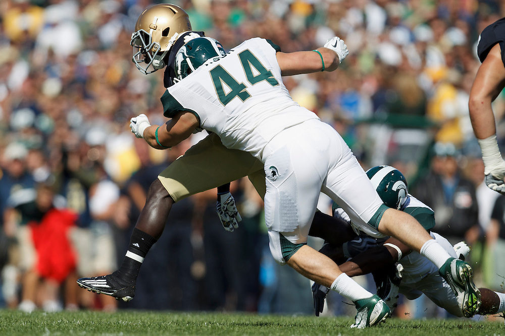 Michigan State linebacker Marcus Rush (#44) makes tackle on Notre Dame wide receiver Theo Riddick (#6) in action during NCAA football game between Notre Dame and Michigan State.  The Notre Dame Fighting Irish defeated the Michigan State Spartans 31-13 in game at Notre Dame Stadium in South Bend, Indiana.