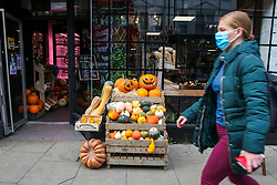 © Licensed to London News Pictures. 12/10/2020. London, UK. A woman wearing a face covering walks past the display of pumpkins outside Mum's Cafe in north London as it prepares for Halloween. The government has announced that trick-and-treating will not be allowed in areas under local lockdown.   <br /> At 3.30pm Prime Minister Boris Johnson will address the House of Commons followed by an address to the public on TV at 6pm where he will outline the three-tier plan with areas in England labelled as medium, high or very high risk, and this will inform the 'appropriate interventions' needed in each area. Photo credit: Dinendra Haria/LNP