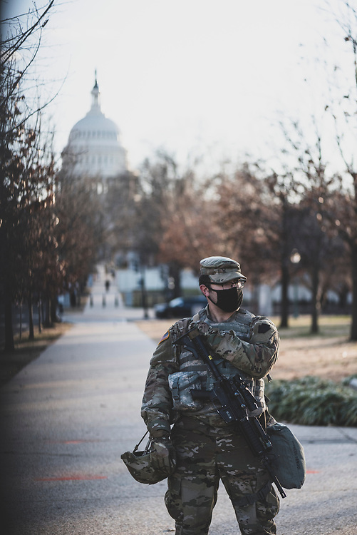 Washington DC, USA - January 18, 2021: A member of the Pennsylvania National Guard stands behind the recently constructed fence surrounding the U.S. Capitol.