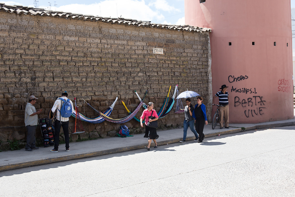 """A street scene in Intibucá outside the city prison, the graffitti on the wall says """"Chepos Asesinos"""" (The Police are Murderers) and """"Berta Vive"""" (Berta Lives). Berta Cáceres campaigned and organised communities in Intibucá and other areas of Honduras to defend indigenous rights and territories before her assassination."""