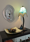The stem of the lamp atop the mirrored console mimics the angle of the mirror on the wall. The lamp was from an art gallery in Madison, Wisconsin and the mirror was a mail-order purchase. The concave glass dish was made by an artist from Ladue. Sheridan and Rikki Glen are At Home in their Tanglewood subdivision home in Caseyville, IL on Wednesday January 16, 2019. <br /> Photo by Tim Vizer