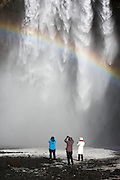 A rainbow appears when the sun breaks through the clouds at Skógafoss in southern Iceland