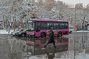 A person wearing surgical face protective mask to curb the spread of coronavirus outbreak in Armenia runs to cross the street as his reflections appear in the melting snow in the Armenian capital Yerevan on Wednesday, Jan 20, 2021. According to John Hopkins University, Coronavirus death rates in Armenia reached up to 164,912 with over 3,000 deaths. (Photo/ Vudi Xhymshiti)