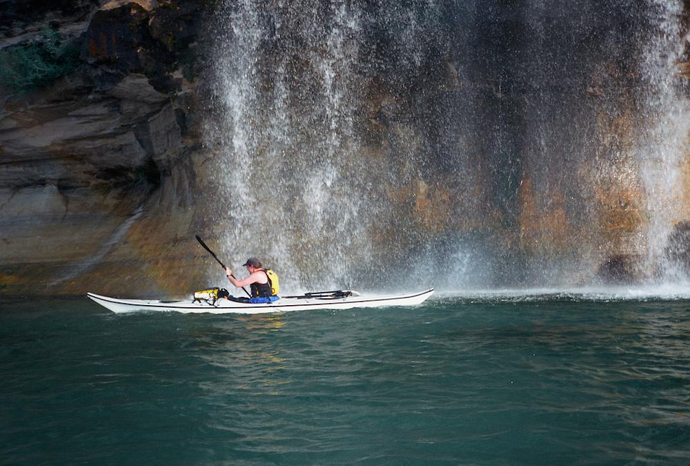 A sea kayaker paddles through Spray Falls in Pictured Rocks National Lakeshore near Munising, Michigan.