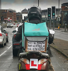 © Licensed to London News Pictures. 1/11/2020. Guildford, UK. A Deliveroo driver displays a message saying 'There's no pandemic - just an attack on our liberties!' as he works in Guildford, Surrey. The government have announced that there will be a one month lockdown in England from November 5th.  Photo credit: Roger Allan/LNP