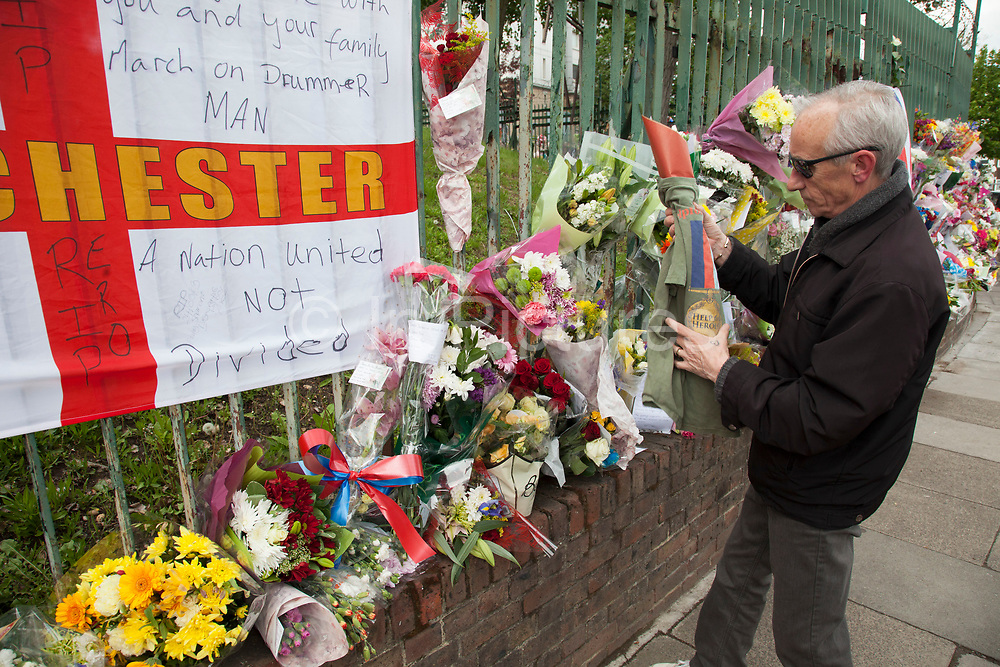 London, UK. Saturday 25th May 2013. Visitor wraps flowers in a Help for Heroes t-shirt at the memorial to Drummer Lee Rigby in Woolwich, London, UK. Flowers from every section of the local community along with messages of condolence and support. On the afternoon of 22 May 2013, Lee Rigby, a British Army soldier and a Drummer of the Royal Regiment of Fusiliers, was killed by two attackers near the Royal Artillery Barracks in Woolwich, south-east London.