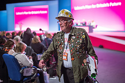 © Licensed to London News Pictures . 24/09/2014 . Manchester , UK . A man with numerous badges and stickers on his jacket and a hard hat at the conference . The Labour Party Conference 2014 . Photo credit : Joel Goodman/LNP