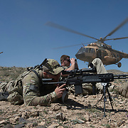 A coalition member from the Train, Advise, Assist Command - Air, guides a Afghan Air Force Mi-17 onto the landing zone, while US Army Soldiers provide security, April 9, 2015, at a training range outside of Kabul, Afghanistan. The AAF demonstrated the capabilities of the MD-530F's two FN M3P .50 Cal machine guns to local media and Afghan military leaders. (U.S. Air Force Photo by Staff Sgt. Perry Aston/Released)