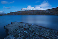 Snow covered mountain rise above lake Radujavri along Kungsleden trail, Lappland, Sweden