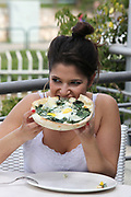 Young woman eats a pizza pie with spinach and egg