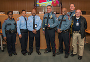 Houston ISD Police officer Gilbert Garcia poses for a photograph with PD staff after he was recognized during a Central Office staff meeting, April 8, 2014.