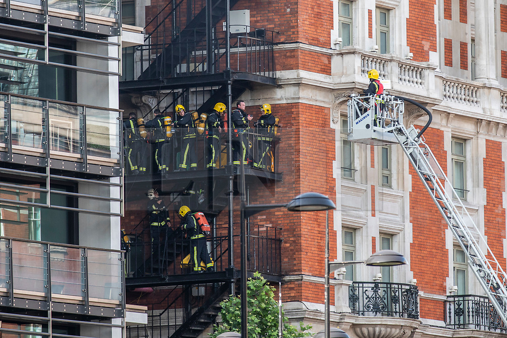 © Licensed to London News Pictures. 06/06/2018. London, UK. Firemen gather on the fire escape of the Mandarin Oriental Hotel in Knightsbridge where a fire has broken out. Photo credit: Rob Pinney/LNP