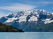 Glaciers in the Chugach Mountains melt into Barry Arm of Prince William Sound, Alaska, USA. Prince William Sound is surrounded by Chugach National Forest (the second largest national forest in the USA). Tour spectacular Prince William Sound by commercial boat from Whittier, which sits strategically on Kenai Peninsula at the head of Passage Canal. Whittier is a port for the Alaska Marine Highway System, a ferry service which operates along the south-central coast, eastern Aleutian Islands, and the Inside Passage of Alaska and British Columbia, Canada. Cruise ships stop at the port of Whittier for passenger connections to Anchorage (by road 60 miles) and to the interior of Alaska via highway and rail (the Denali Express). Known by locals as the Whittier tunnel or the Portage tunnel, the Anton Anderson Memorial Tunnel links Whittier via Portage Glacier Highway to the Seward Highway and Anchorage. At 13,300 feet long (4050 m), it is the longest combined rail and highway tunnel in North America. Whittier was severely damaged by tsunamis triggered by the 1964 Good Friday Earthquake, when thirteen people died from waves reaching 43 feet high (13 meters).