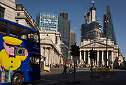 With the Bank of England on the left and neo-classical columns of Cornhill Exchange beneath new skyscrapers rising above the City of London - the capitals financial district aka The Square Mile, a London sightseeing bus passes through Bank Triangle with on 19th April 2018, in London, England.