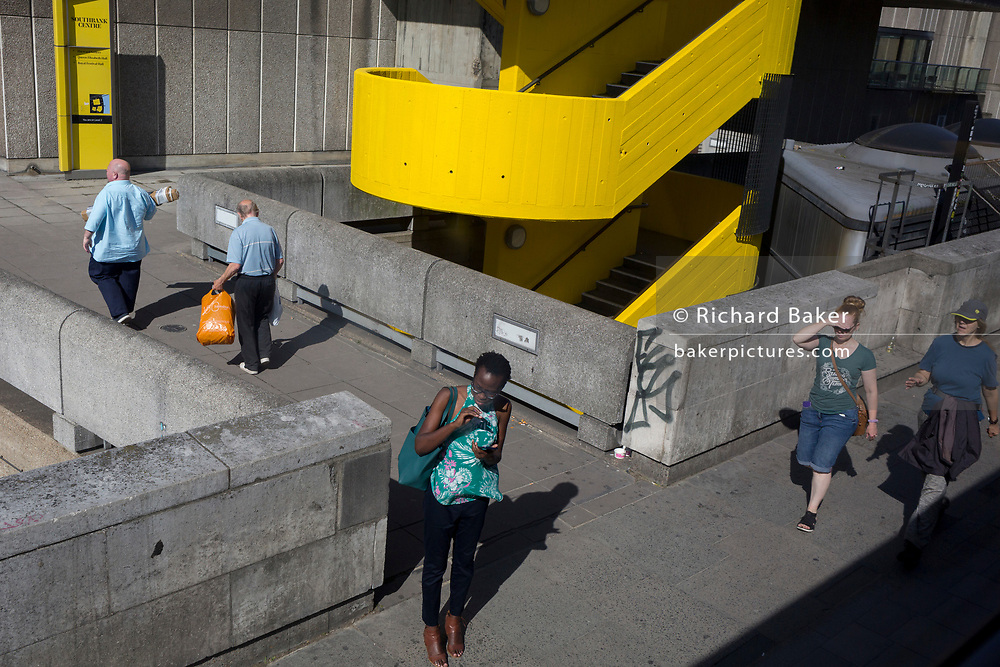 Passers-by walk along the grey and yellow concrete architecture of the Southbank Centre in Lambeth, on 22nd August 2019, in London, England.