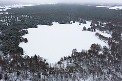 Aviemore, Scotland, UK. 4 February 2021. Loch Vaa is completely frozen and offers opportunity to walk across it. A small boathouse is now icebound and three ladies from the InVaa Dookers wild swimming group use axes to break the ice to allow them to soak in the icy water for a few minutes. Pic; Aerial view of frozen Loch Vaa.  Iain Masterton/Alamy Live News